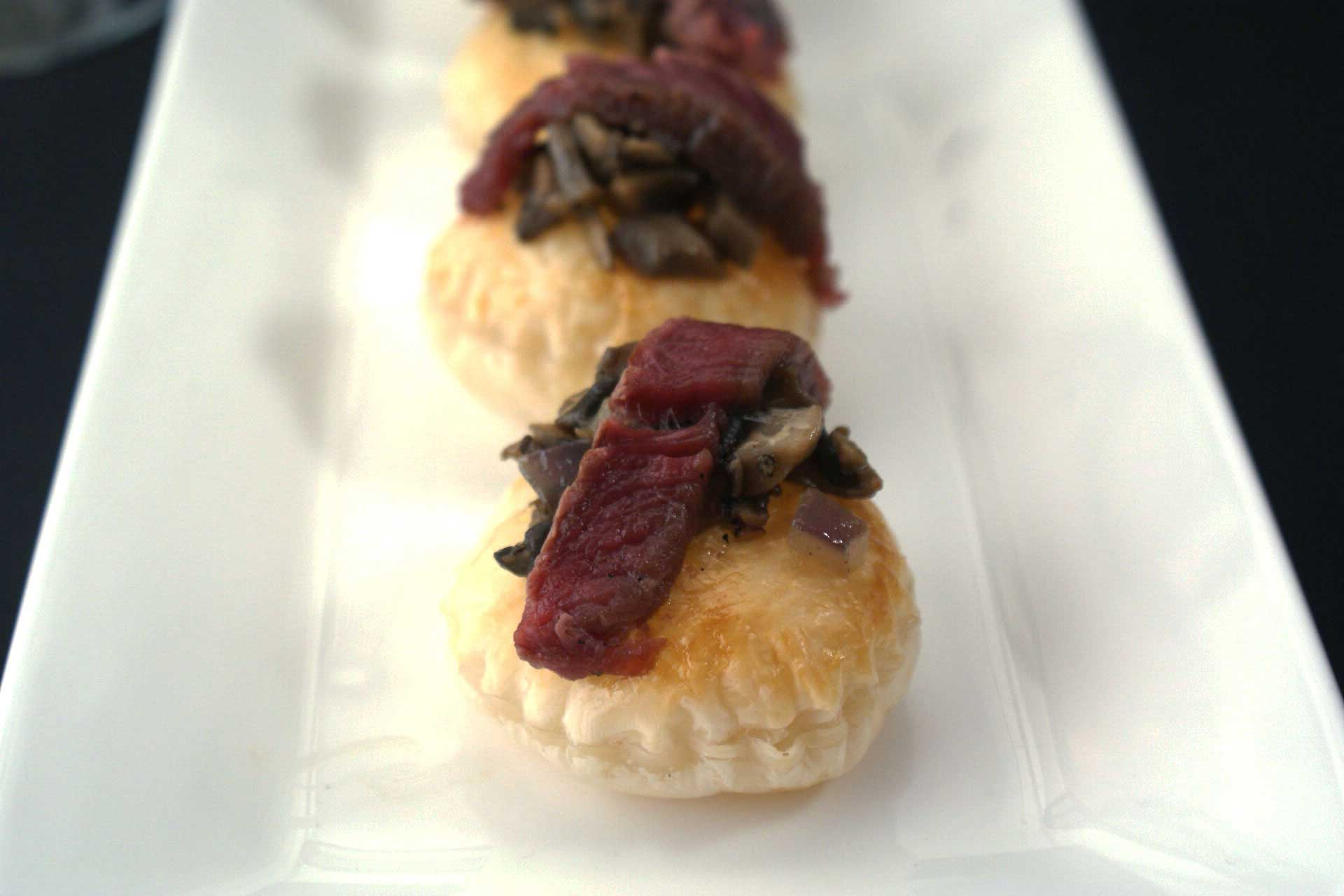 De-constructed Beef Wellington Canapés. Puff pastry disks topped with a mushroom duxelle and a slice of fillet steak.