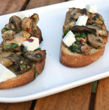 Mushroom Bruschetta. Crisp crostini topped with mozzarella and garlic and parsley cooked mushrooms. A perfect appetizer, great with a glass of wine or a cold beer.
