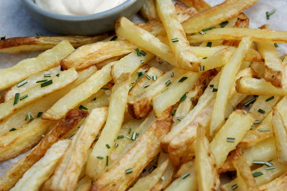 Crispy Oven Baked Fries with Rosemary Salt. The potatoes are oven cooked in coconut oil, making them a healthy side dish.