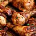 Close up on the crispy marinated peri peri chicken in a metal roasting tin.