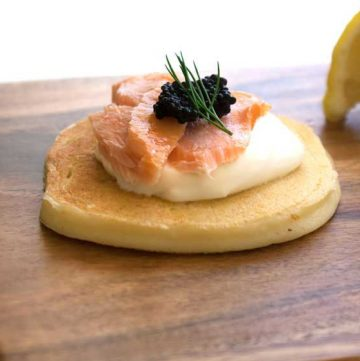 Deliciously light ricotta pancakes, topped with hot smoked salmon and sour cream. A great appetiser that you can prepare in advance. Perfect for the holidays #Christmas #food #recipe
