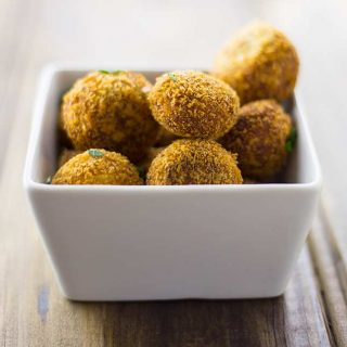 close up a white bowl of golden croquettes