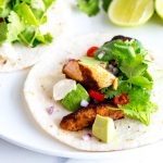 close up on a single blackened salmon taco with cilantro and avocado