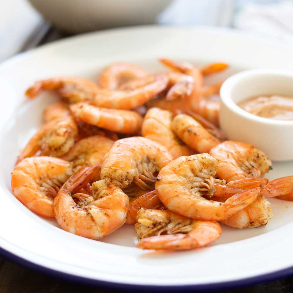 White plate with cooked shell on prawns with a bowl of Old Bay Cocktail sauce on the side.