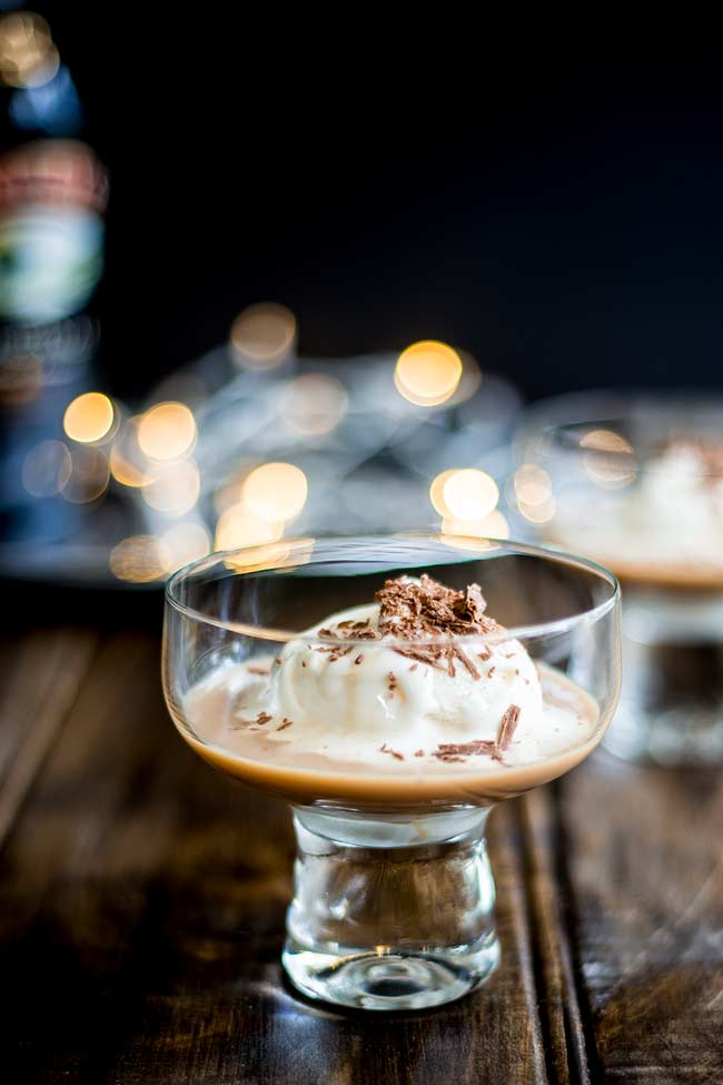 wooden table with a bowl wine glass filled with ice cream and baileys and garnished with chocolate flakes