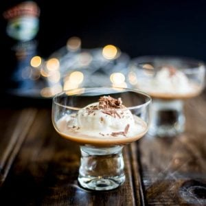 sq picture showing a wooden table with two glasses full of baileys and ice cream with fairy lights in the background