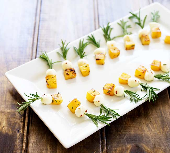 Over head view of the pineapple mozzarella skewers on a white platter set on a wooden table.