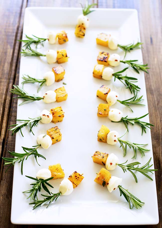 Over head showing full platter with 20 pineapple mozzarella skewers on a white platter set on a wooden table.