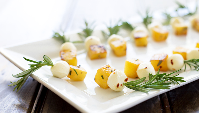Side view of the rosemary skewers showing the charred pineapple