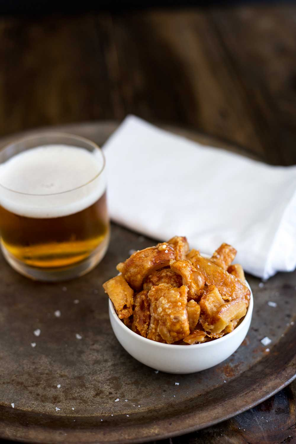 Metal tray with a beer, white napkin and a bowl of crackling bites.