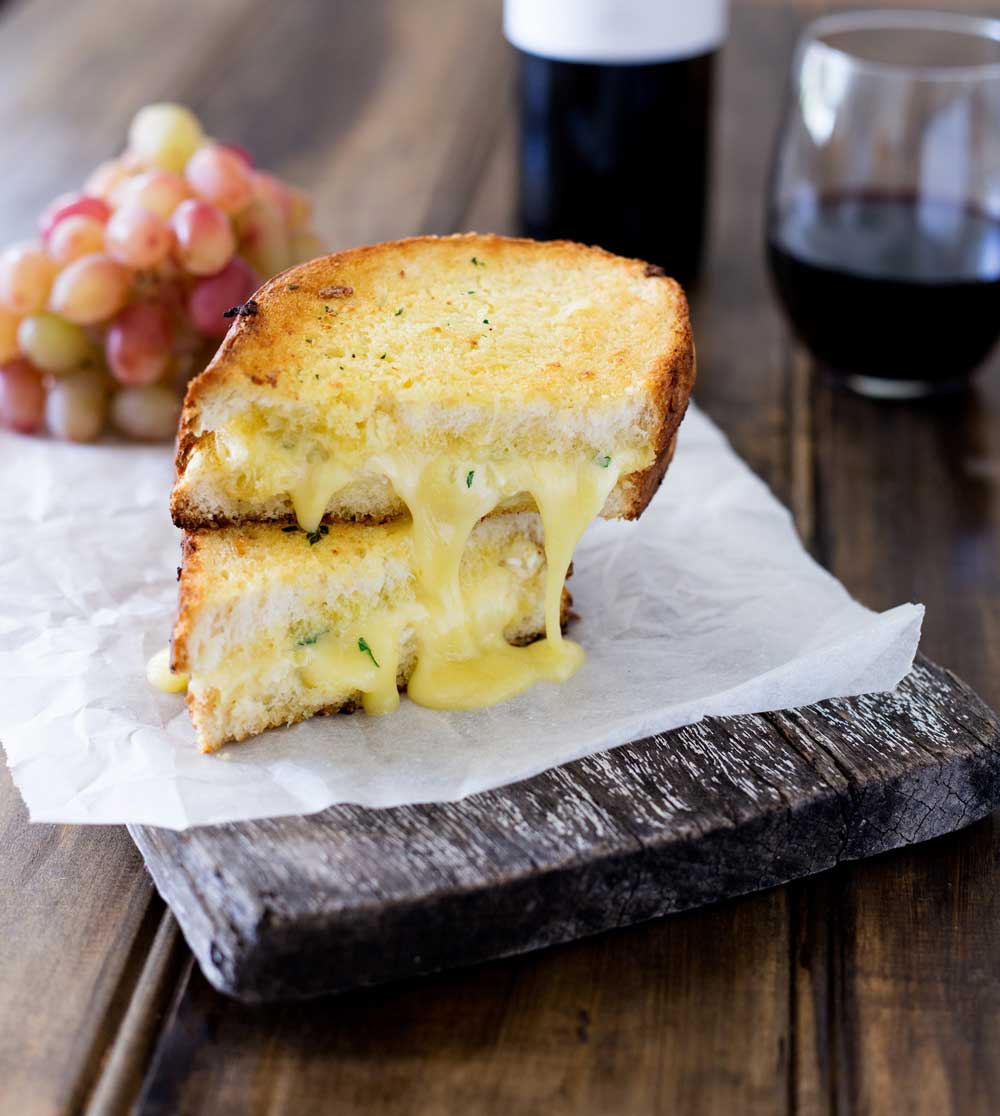 Cheesy garlic bread sandwiches. Garlic butter smothered bread filled with soft brie, crisped and browned to melting gooey perfection. Perfection! I kid you not, this is a sandwich that will make you lick the plate!!!