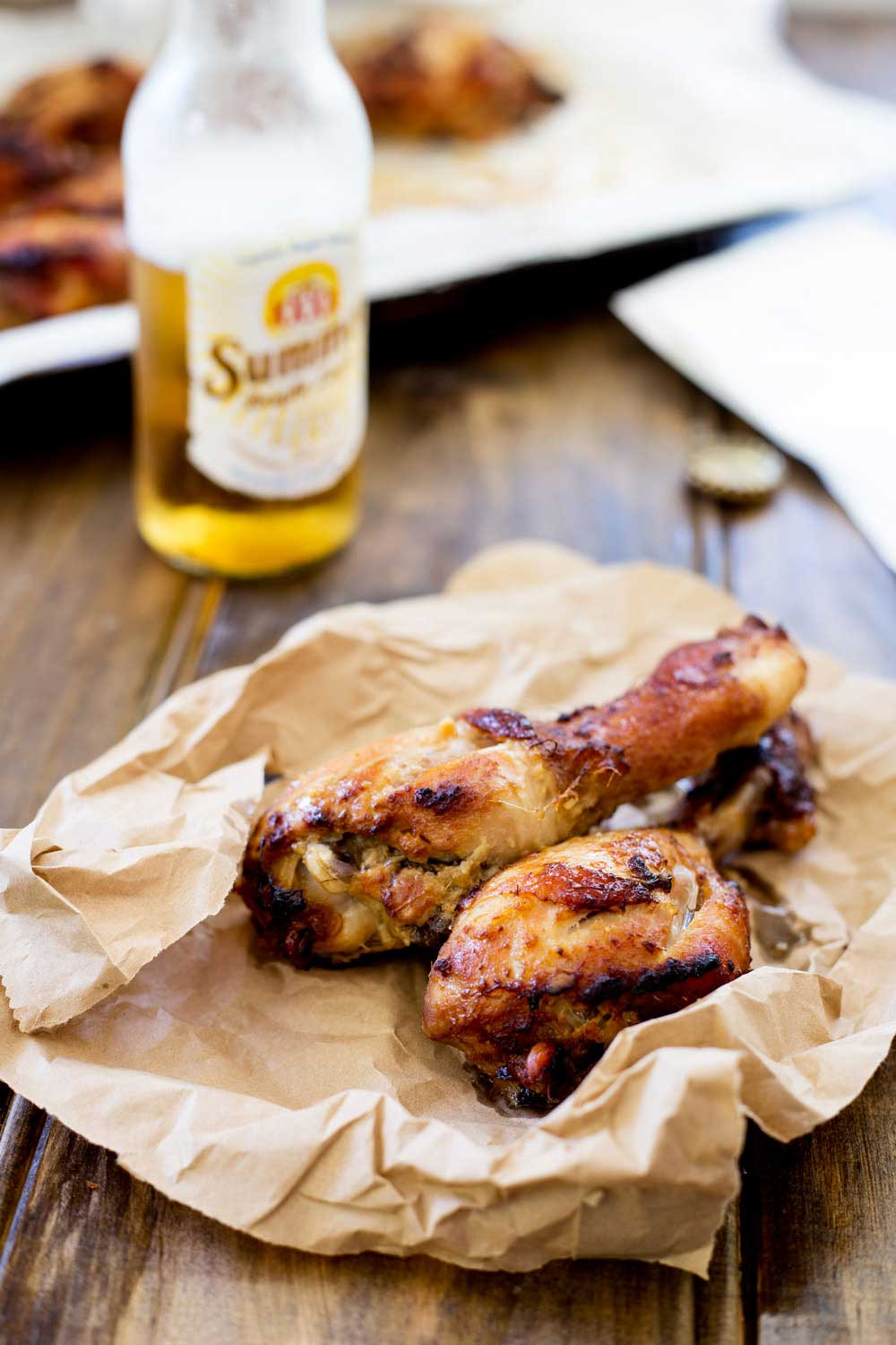 two baked ginger chicken drumsticks on a brown piece of paper with beer in the background