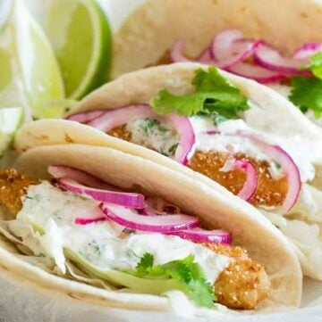 These fish tacos are taco heaven! Soft flour tortillas are filled with crispy fish, sweet and sour brown sugar onions and an amazing creamy taco sauce.