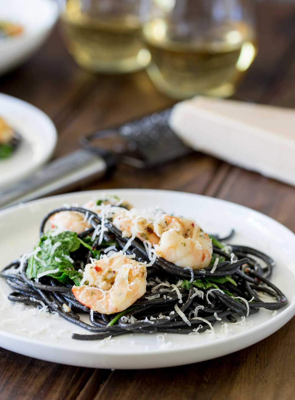 Spaghetti Nero with shrimp and arugula on a white plate with parmesan in the background