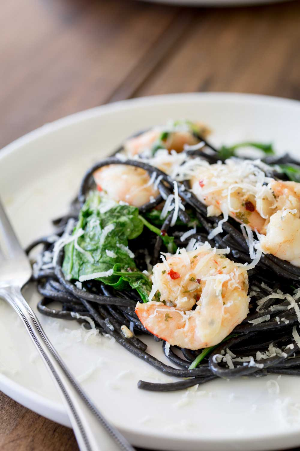 Close up on the seared shrimp on top of a bed of squid ink pasta