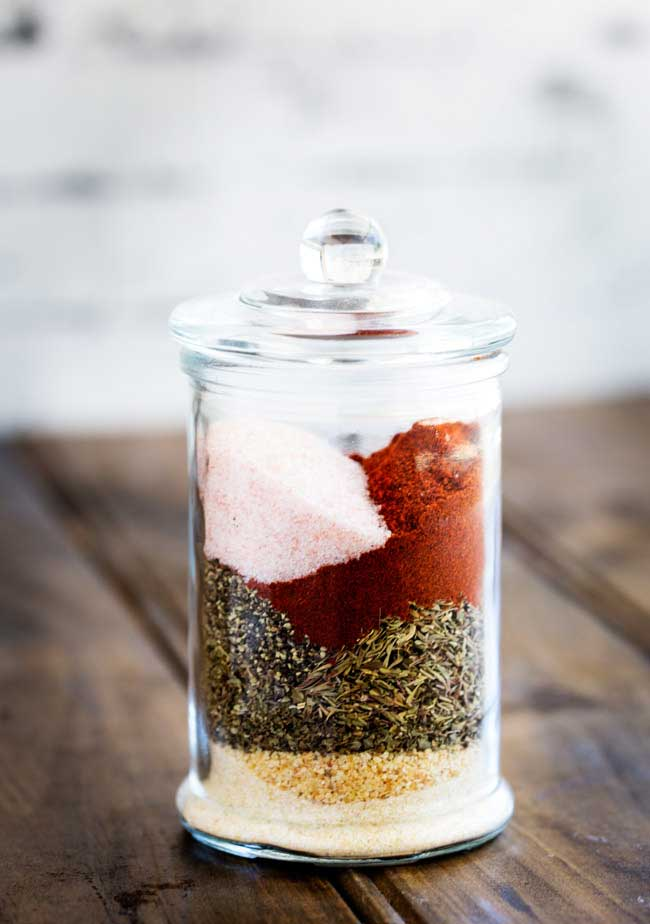 A tall jar with individual spices layered inside