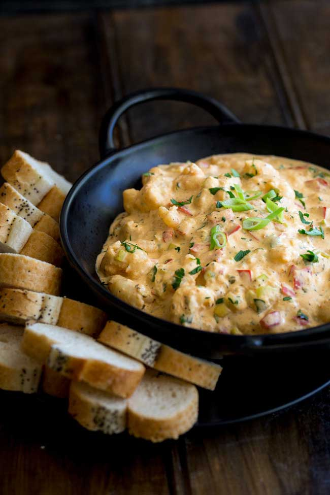 Black bowl with handles filled with a creamy Hot Louisiana shrimp dip with bread on the side.