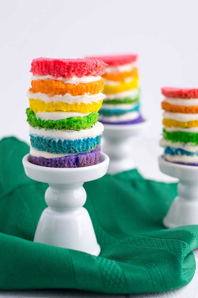 white table with green napkin and 3 mini rainbow cakes on it.