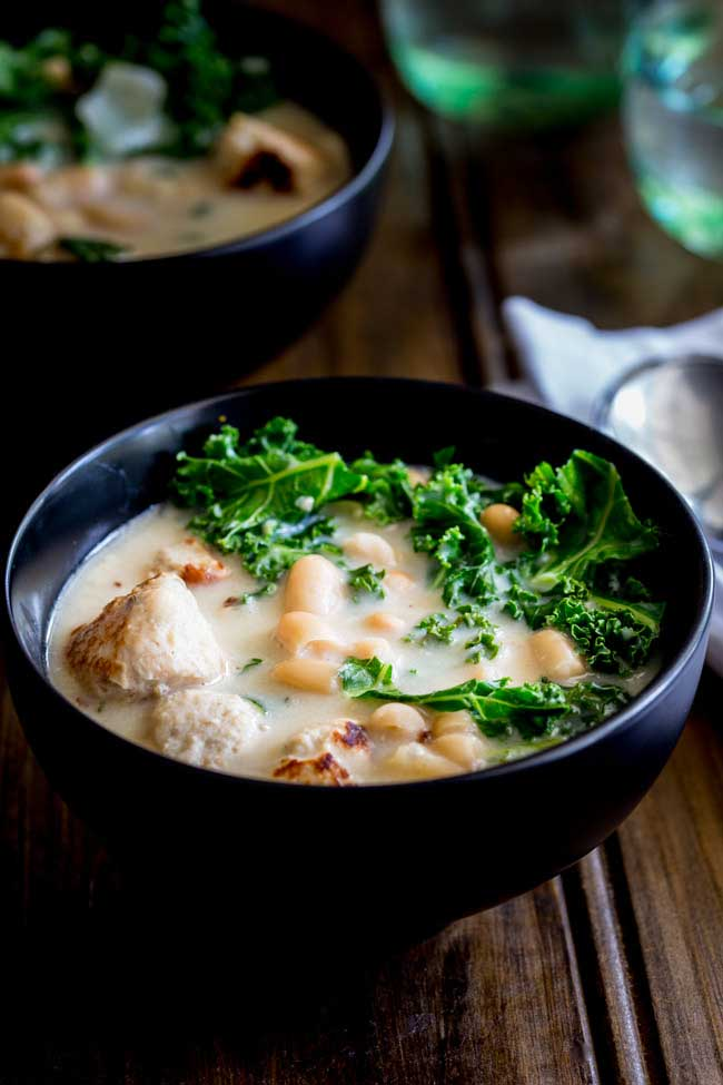 black bowl of creamy soup with chicken sauces chunks, white beans and green kale on top