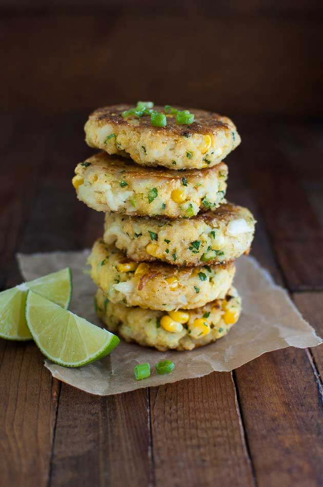 A stack of crab and sweetcorn cakes on a sheet of paper on a wooden table
