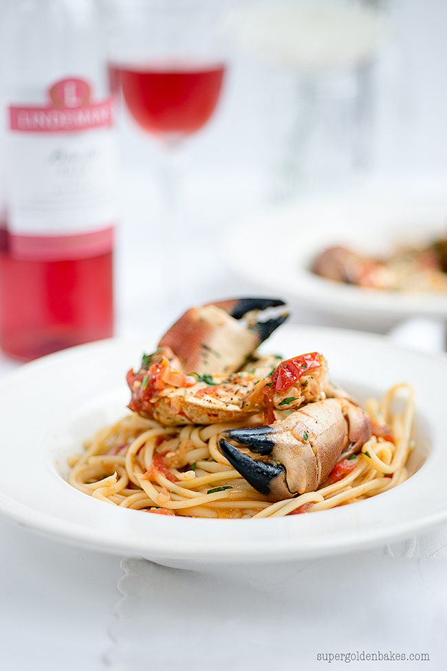 Crab claws sat on a bowl of tomato pasta