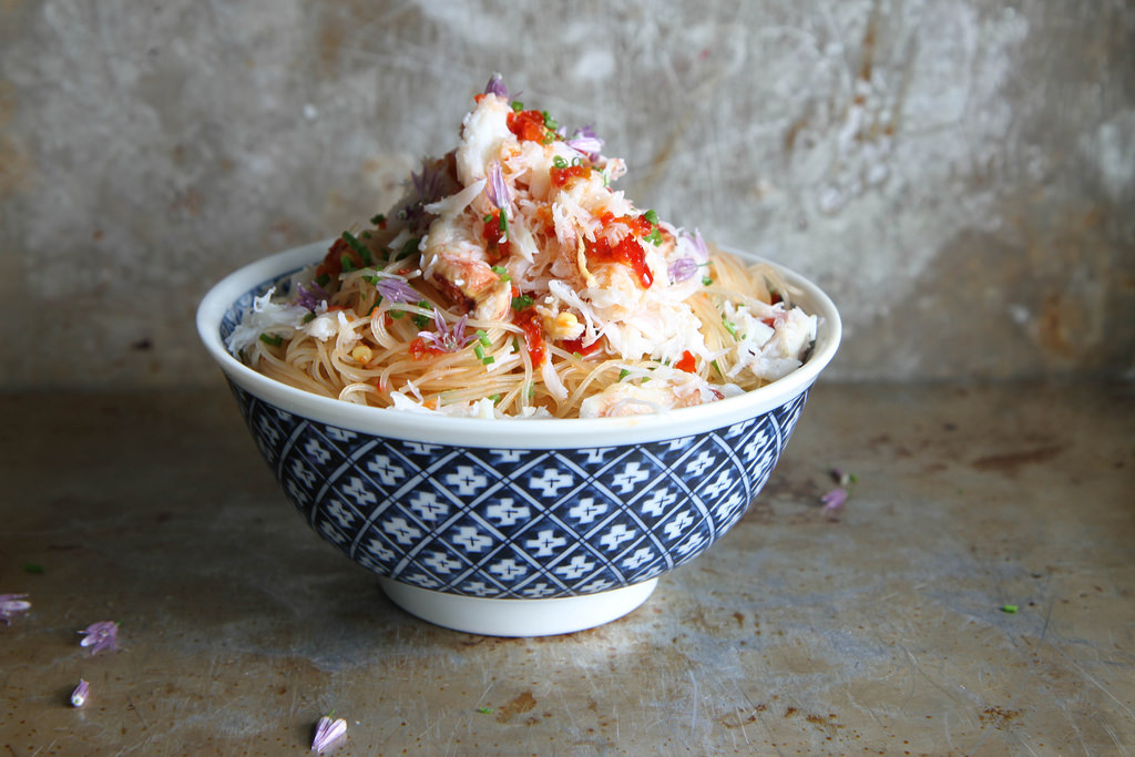 a blue and white bowl filled with thin noodles and topped with crab and chilli