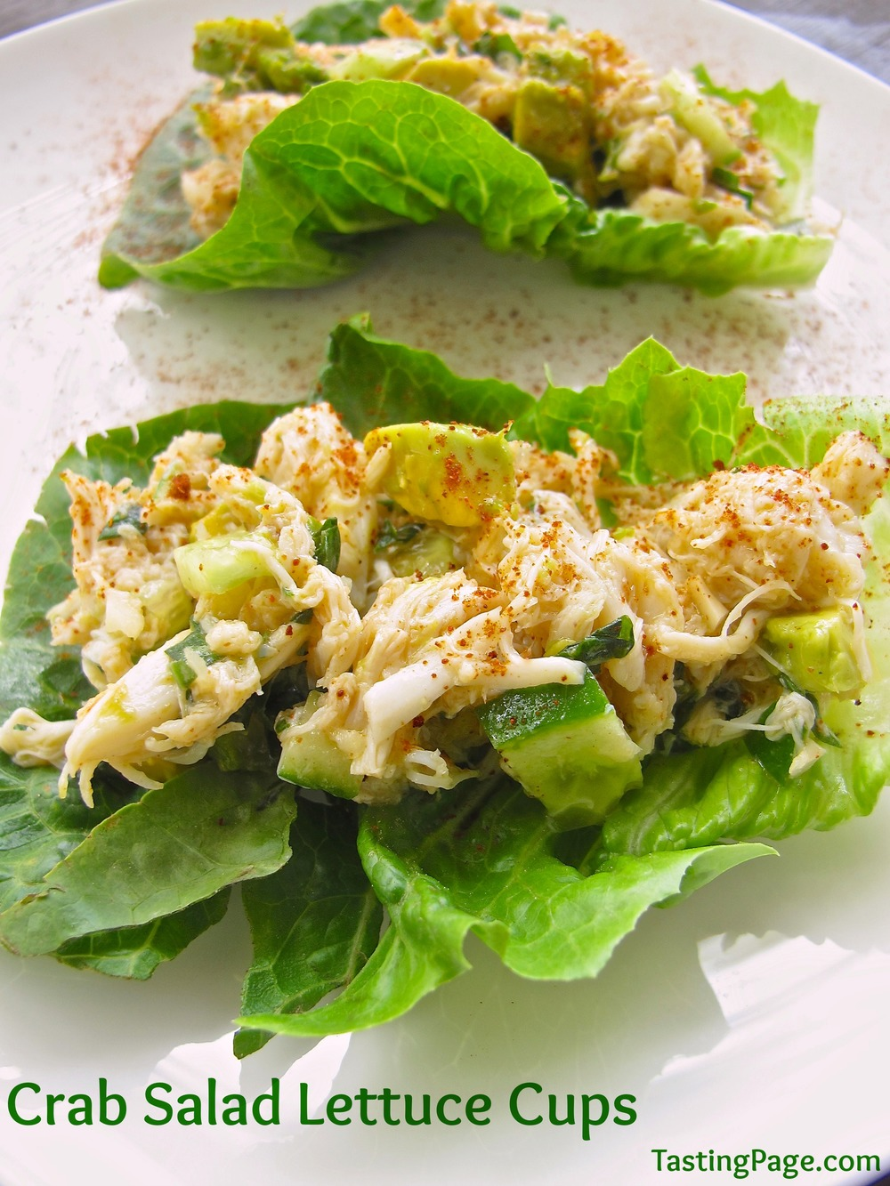 crab and cucumber salad sat inside lettuce cups on a white plate, garnished with paprika