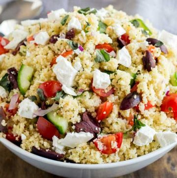 Close up of the tomatoes and cucumber in this greek couscous salad.