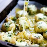 squashed garlic butter potatoes in a metal roasting tin, smothered with cheese