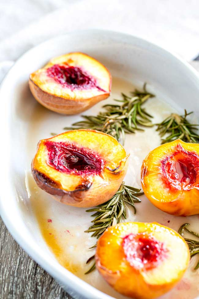 4 roasted peach halves in a white oval baking dish