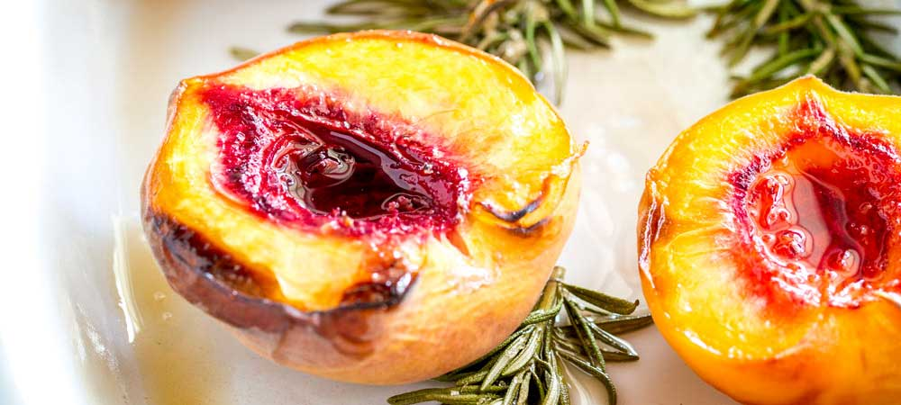 Roasted Peaches with Brown Sugar and Rosemary - Tender peaches sprinkled with brown sugar and roasted on rosemary sprigs to create a sweet and floral syrup. The perfect dessert for the late summer and early fall evenings. Add a dollop of thick cream and enjoy the sweet yielding fragrant fruit. From Sprinkles and Sprouts