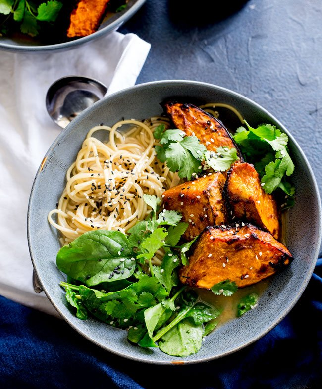 Overhead showing a pile of noodles garnished with sesame seeds and some charred roasted pumpkin. All in a rustic blue/grey bowel