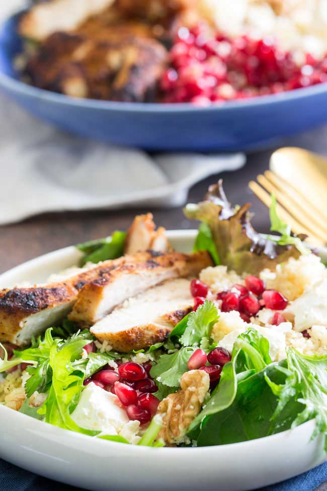 a white plate of salad with chicken, pomegranate walnuts and feta on it