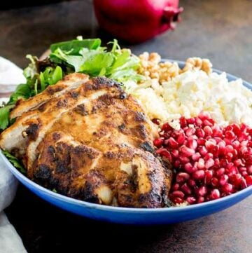 This Moroccan Chicken Couscous Buddha Bowl is there perfect lunch. The chicken is marinated in wonderful moroccan seasoning, whist the sweet tart pomegranate and salty feta round out the dish.  Served onto of a bed of couscous with plenty of fresh salad and herbs, this moroccan buddha bowl is sure to leave you feeling satisfied. Recipe from Sprinkles and Sprouts | Delicious food for easy entertaining.