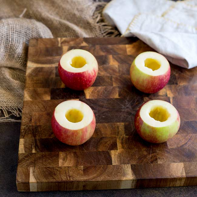 Raw apples on a wooden chopping board with the cores removed.