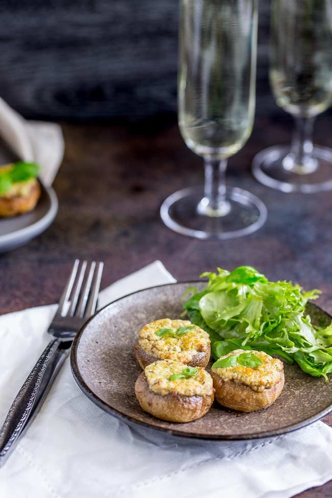 Table setting with 3 Basil and cheese stuffed mushrooms served as a vegetarian appetizer with a small side salad.