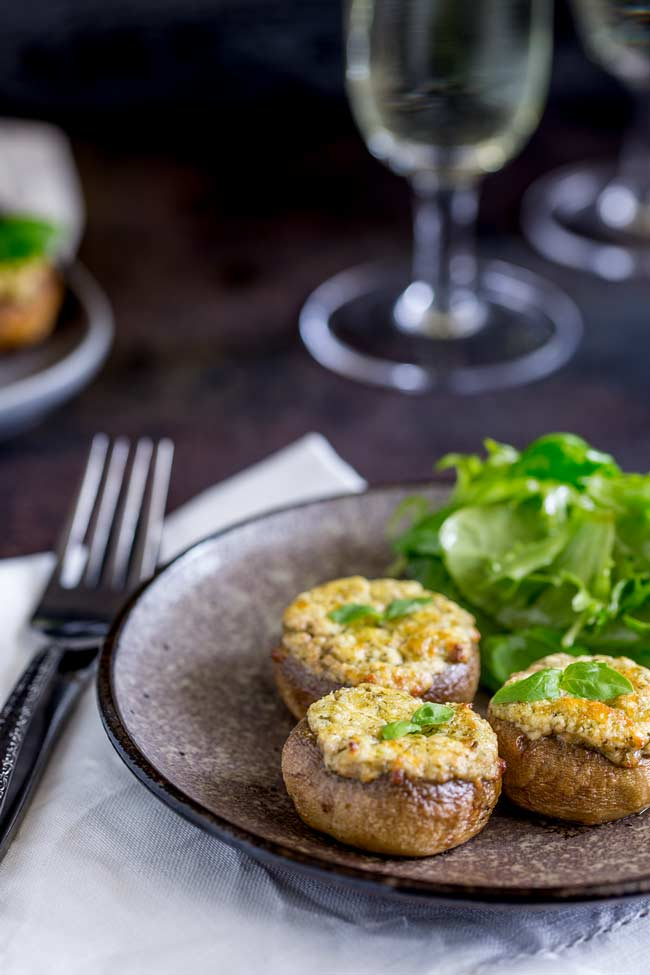 A grey plate with dressed salad and 3 basil and cheese stuffed mushrooms. Wine in backdrop and a second plate of cheese stuffed mushrooms.