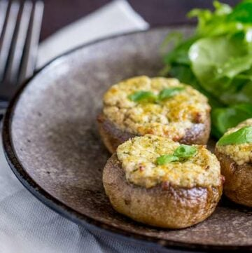 Small thumbnail picture of 3 basil and cheese stuffed mushrooms on a grey plate with a side salad.