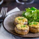Square picture of 3 basil and cheese stuffed mushrooms on a grey plate with a side salad.
