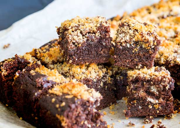 Close up on a cut chocolate brownie with crunchy salted panko topping.