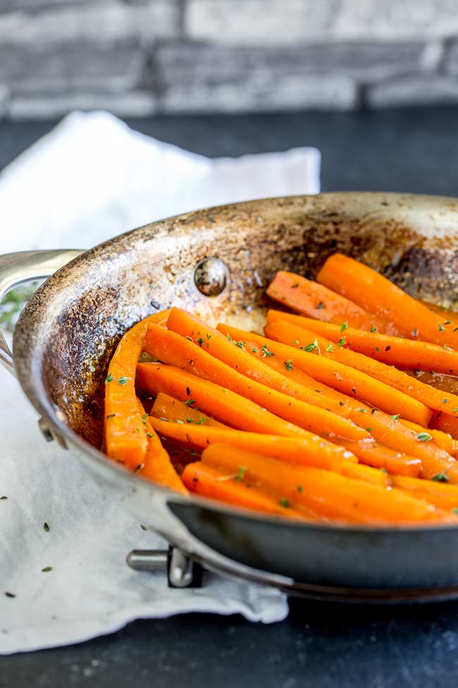 Glazed carrots in a silver sauté pan.