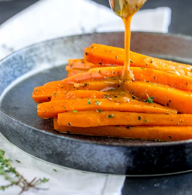 Close up on the brown sugar drizzle hitting the glazed carrots.