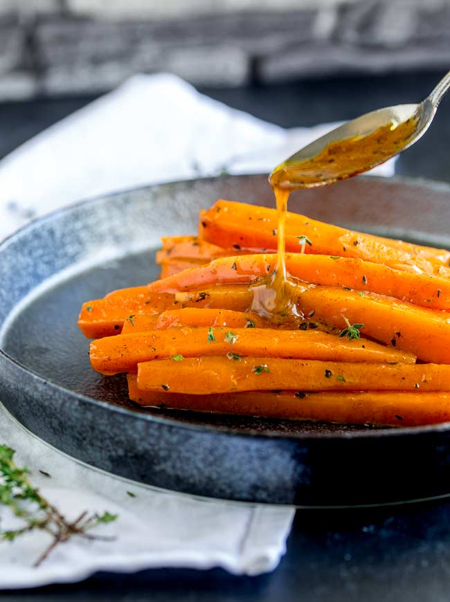 Glazed carrots on a black metal plate with a brown sugar drizzle being poured over them.