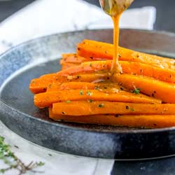 Square image of glazed carrots on a metal plate.