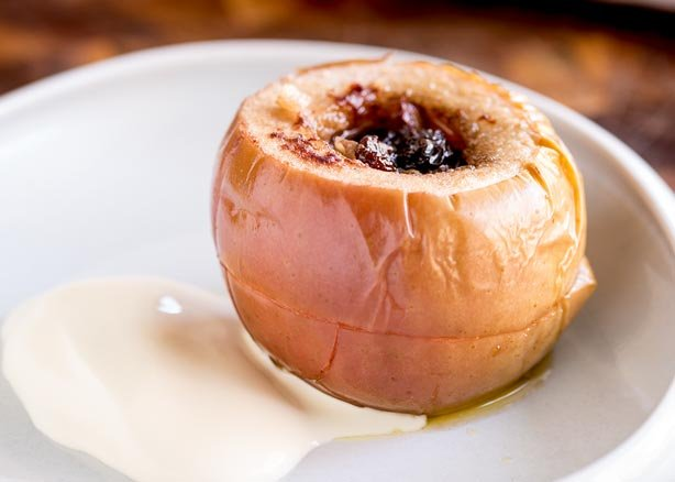 FEATURE IMAGE - Close up of a Slow Cooked Apple stuffed with Walnuts and Sultanas, served on a plate with cream.