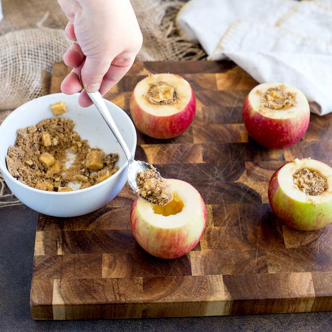 Raw apples on a wooden chopping board, being filled with brown sugar, butter, walnut and sultanas.