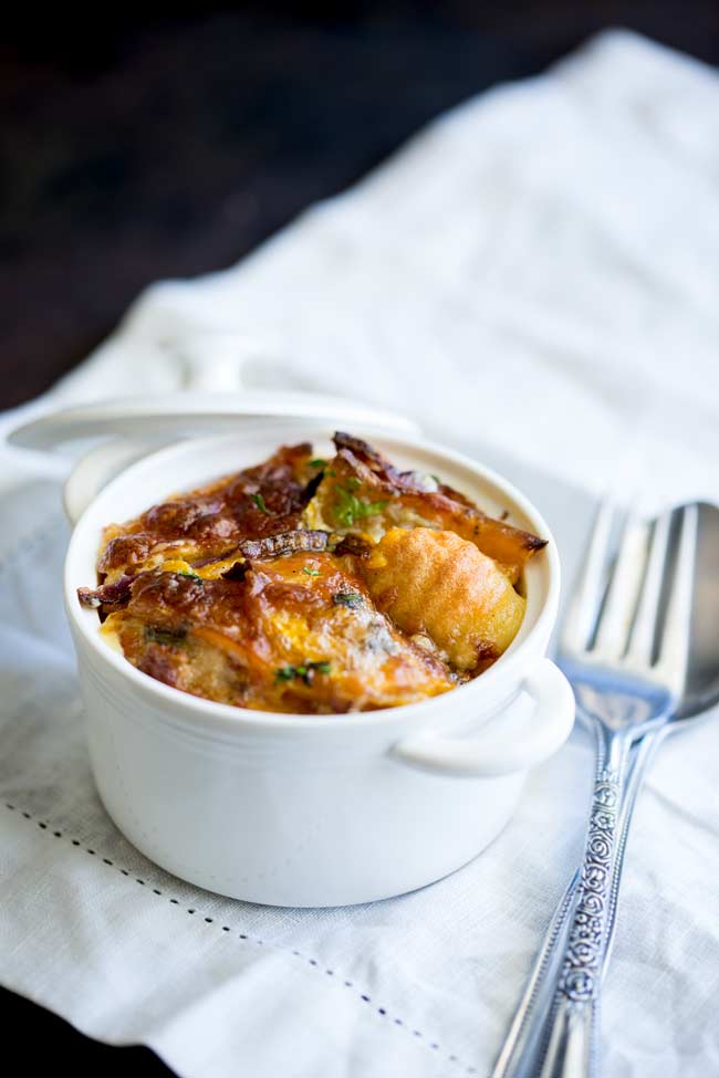 Large white ramekin with an individual serving of Baked Pumpkin Gnocchi.