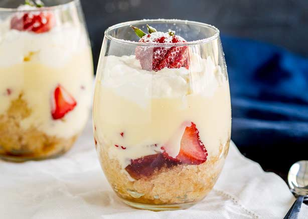 Individual Strawberry trifle served in a wine glass with a blue background.