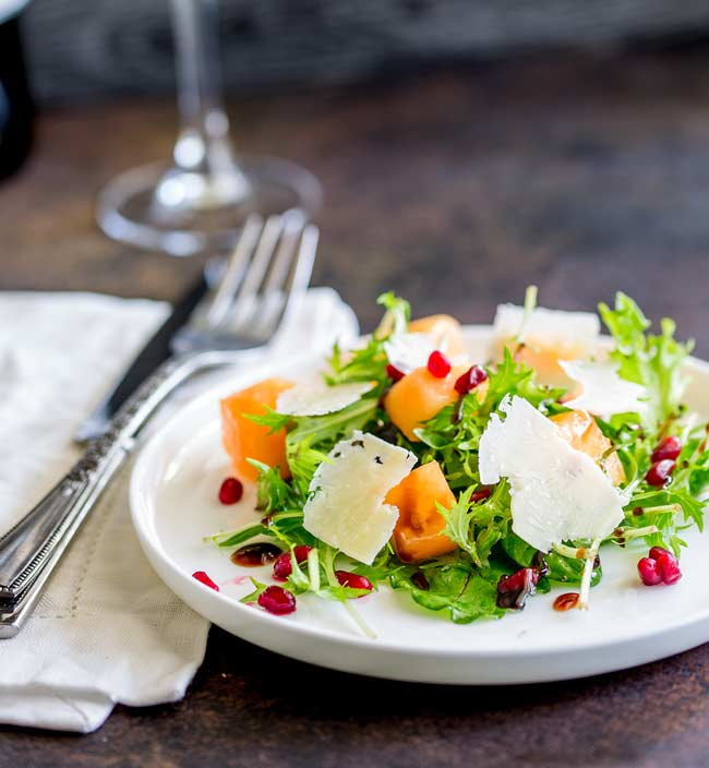 A white plate with green leaves, Cantaloupe melon and pomegranate salad. Wine Glass in the background with a linen napkin and ornate cutlery.