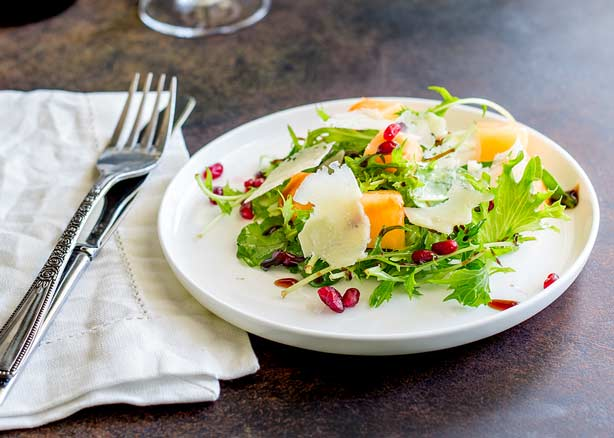Feature image, showing the Melon and Pomegranate salad on a white plate.